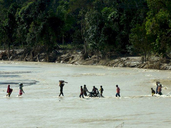 FOTO: Pengungsi Masamba Harus Menyeberangi Sungai untuk Dapat Bantuan