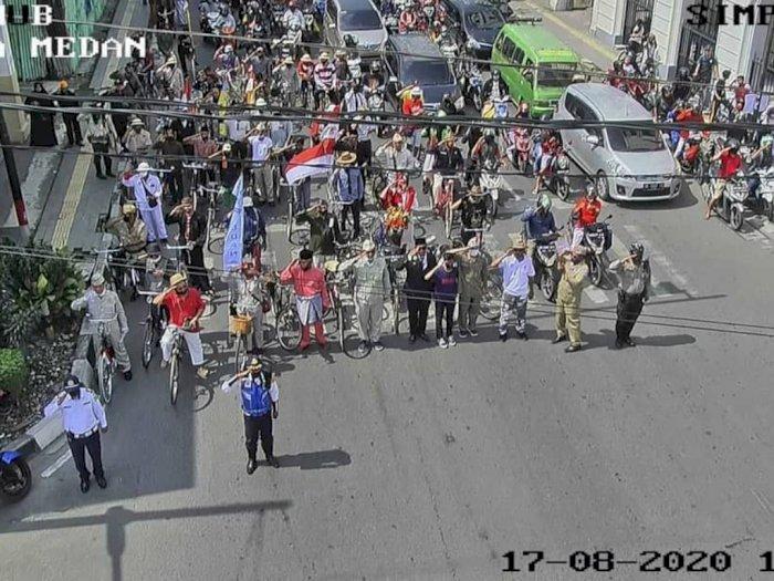 FOTO: Traffic Light di Medan Dimerahkan, Para Pengendara Berikan Tanda Penghormatan
