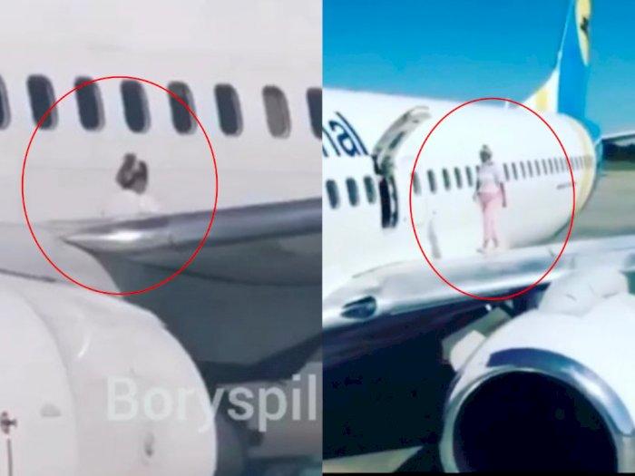 Viral Video Wanita Buka Pintu Darurat & Duduk di Sayap Pesawat, Aksinya Konyol!