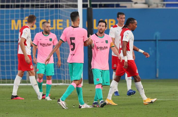 Pemain Barcelona Lionel Messi merayakan gol kedua mereka dengan Sergio Busquets