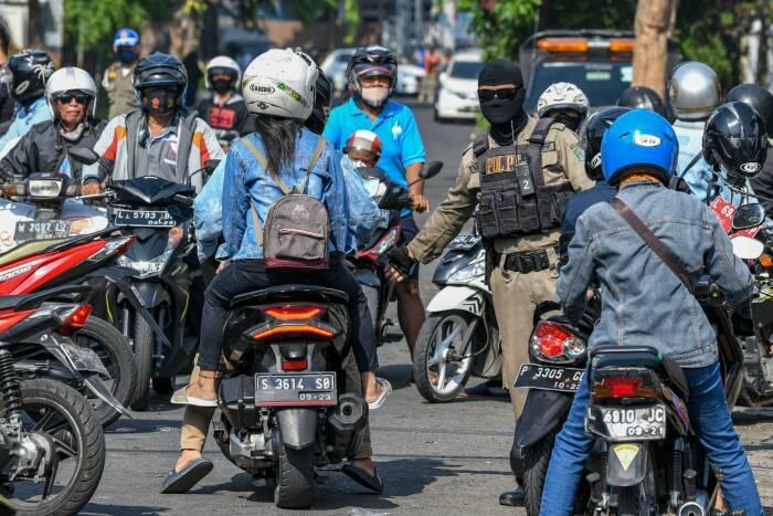 Petugas Satuan Polisi Pamong Praja (Satpol PP) mengarahkan pengendara sepeda motor untuk mengikuti tes usap (swab test) COVID-19 di kawasan Pasar Keputran