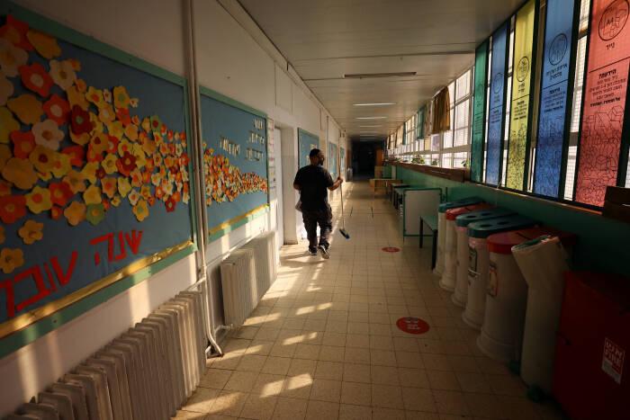 Seorang pria membersihkan sekolah yang ditutup
