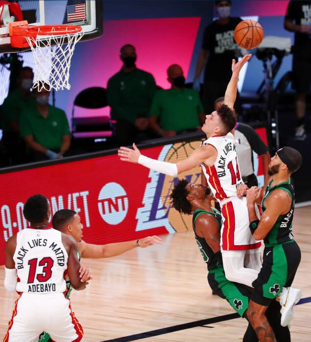 Guard Miami Heat Tyler Herro (14) melakukan pelanggaran ofensif melawan guard Boston Celtics Jaylen Brown (7)