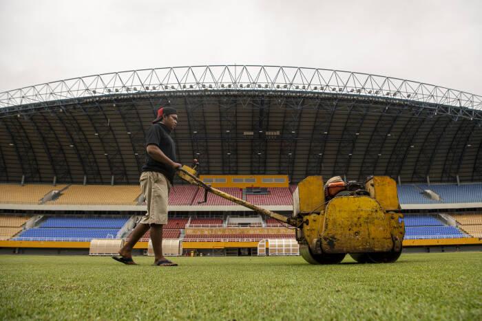 Pekerja melakukan perawatan rumput Stadion Gelora Sriwijaya Jakabaring (GSJ), Jakabaring Sport City (JSC), Palembang, Sumatera Selatan, Senin (21/9/2020).