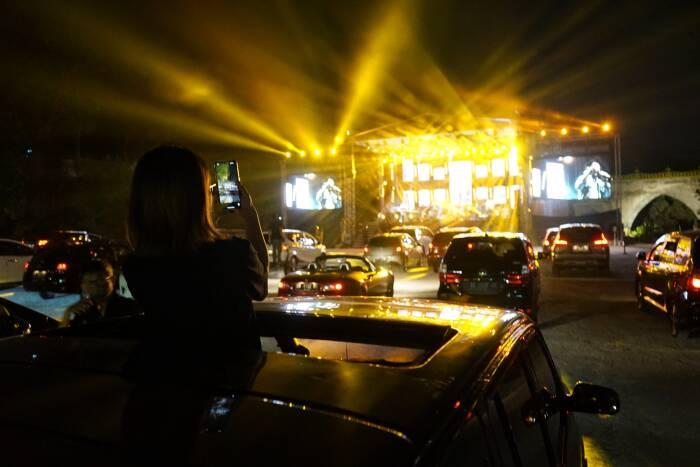 Penonton menyaksikan penampilan band Jikustik dari dalam mobil saat konser musik drive-in di Sleman City Hall, D.I Yogyakarta, Minggu (20/9/2020).