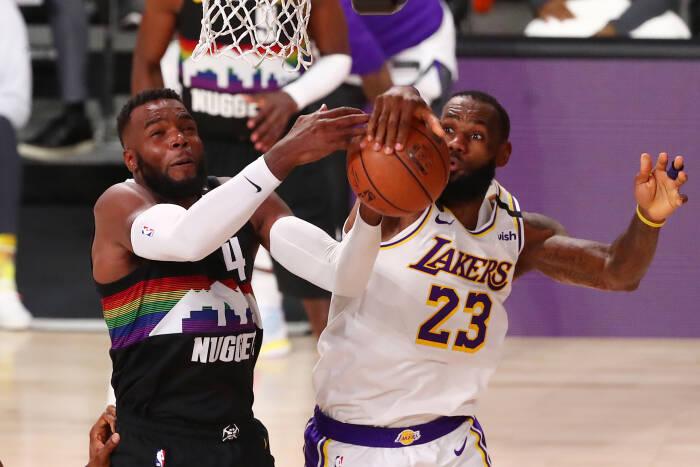 Penyerang Denver Nuggets Paul Millsap (4) dan penyerang Los Angeles Lakers LeBron James (23) berjuang untuk rebound
