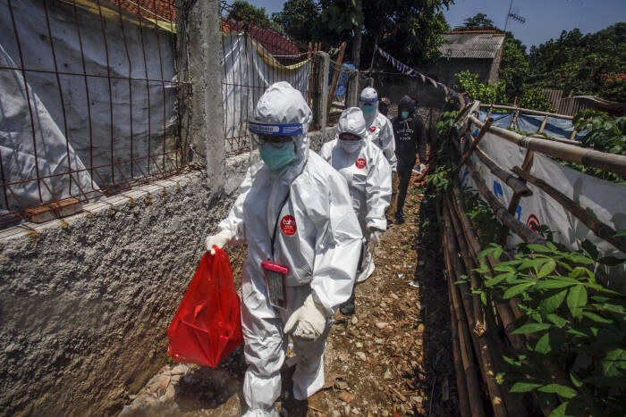 Petugas Dinas Kesehatan Kabupaten Bogor berjalan menuju rumah warga saat akan melakukan test swab di Bojong Gede