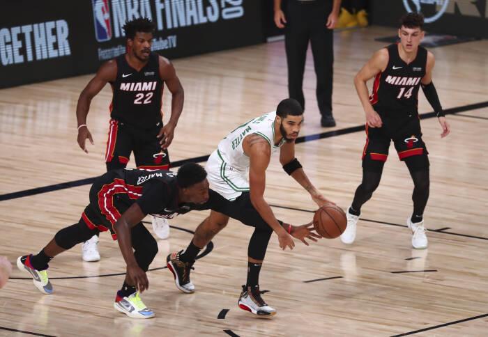 Penyerang Miami Heat Bam Adebayo (13) berebut bola melalui dribel oleh penyerang Boston Celtics Jayson Tatum (0)