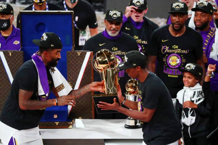 Guard Los Angeles Lakers JR Smith (21) dan guard Rajon Rondo (9) memegang trofi setelah pertandingan keenam Final NBA 2020