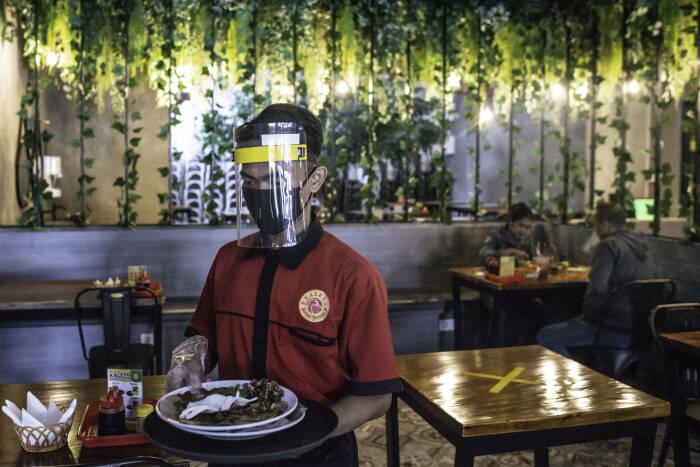Pramusaji membawa piring kotor di restoran Bebek Kaleyo, Kemanggisan, Jakarta, Senin (12/10/2020).