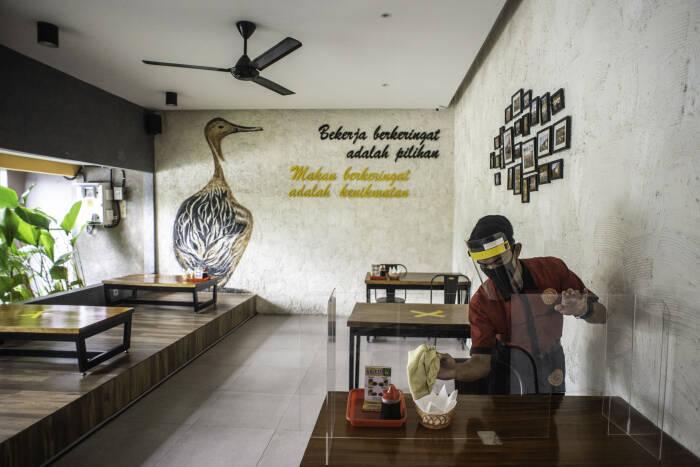 Pramusaji membersihkan mika pembatas meja makan di restoran Bebek Kaleyo, Kemanggisan, Jakarta, Senin (12/10/2020). ANTARA FOTO/Aprillio Akbar