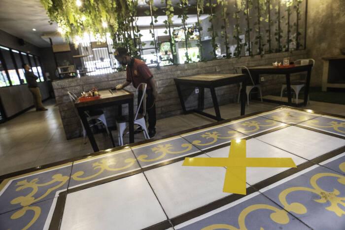 Pramusaji membersihkan meja makan di restoran Bebek Kaleyo, Kemanggisan, Jakarta, Senin (12/10/2020).