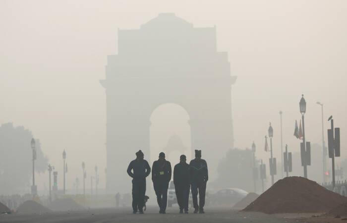 Para pria berjalan di depan Gerbang India yang diselimuti kabut asap di New Delhi