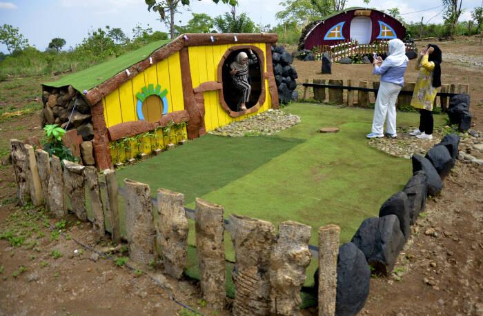 Wisatawan berfoto dengan latar suasana rumah hobbit di obyek wisata Bollangi