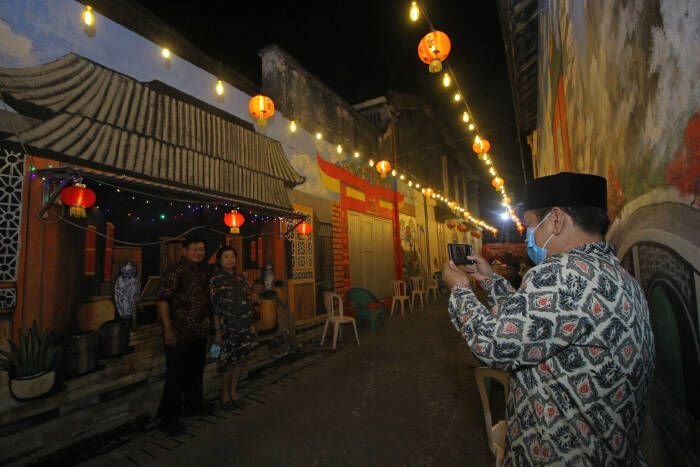 Pengunjung berfoto di depan salah satu mural bernuansa Tionghoa