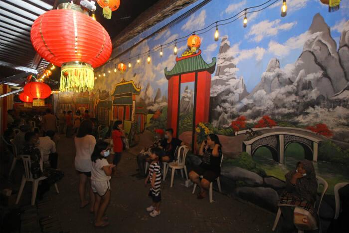 Pengunjung berada di salah satu gang kampung yang dihias dengan mural bernuansa Tionghoa