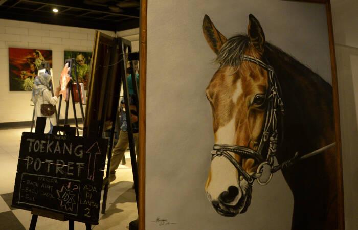 Pengunjung memperhatikan karya lukisan yang dipamerkan