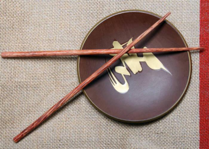 Menyilangkan sumpit di atas piring atau mangkuk.