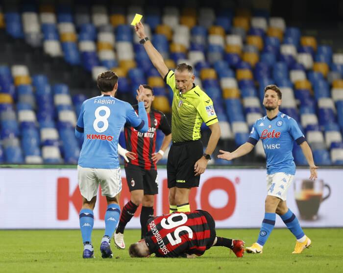 Wasit menunjukkan kartu kuning sementara Alexis Saelemaekers dari AC Milan bereaksi di lapangan