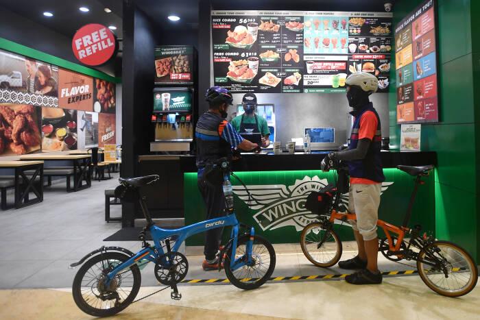 Pesepeda membeli makanan sambil membawa sepedanya di Mal Kuningan City, Jakarta Selatan, Sabtu (28/11/2020).