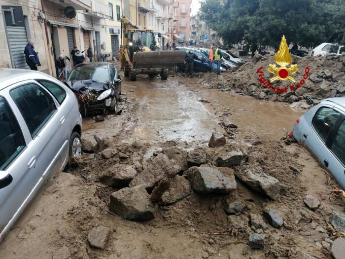 Buldoser menghilangkan lumpur dan puing-puing dari jalan yang banjir