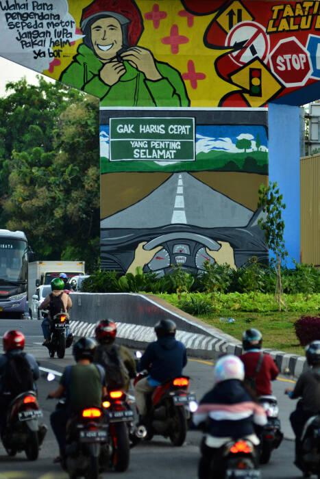 Sejumlah kendaraan melintasi mural bertema taat berlalu lintas