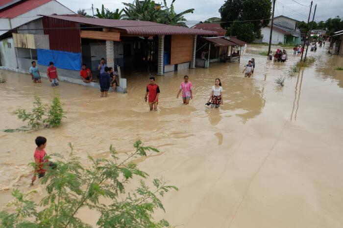 Warga melintasi banjir yang merendam pemukiman penduduk di Kecamatan Sunggal