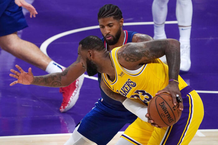 Penyerang Los Angeles Lakers LeBron James (23) mengontrol bola melawan guard LA Clippers Paul George (13)
