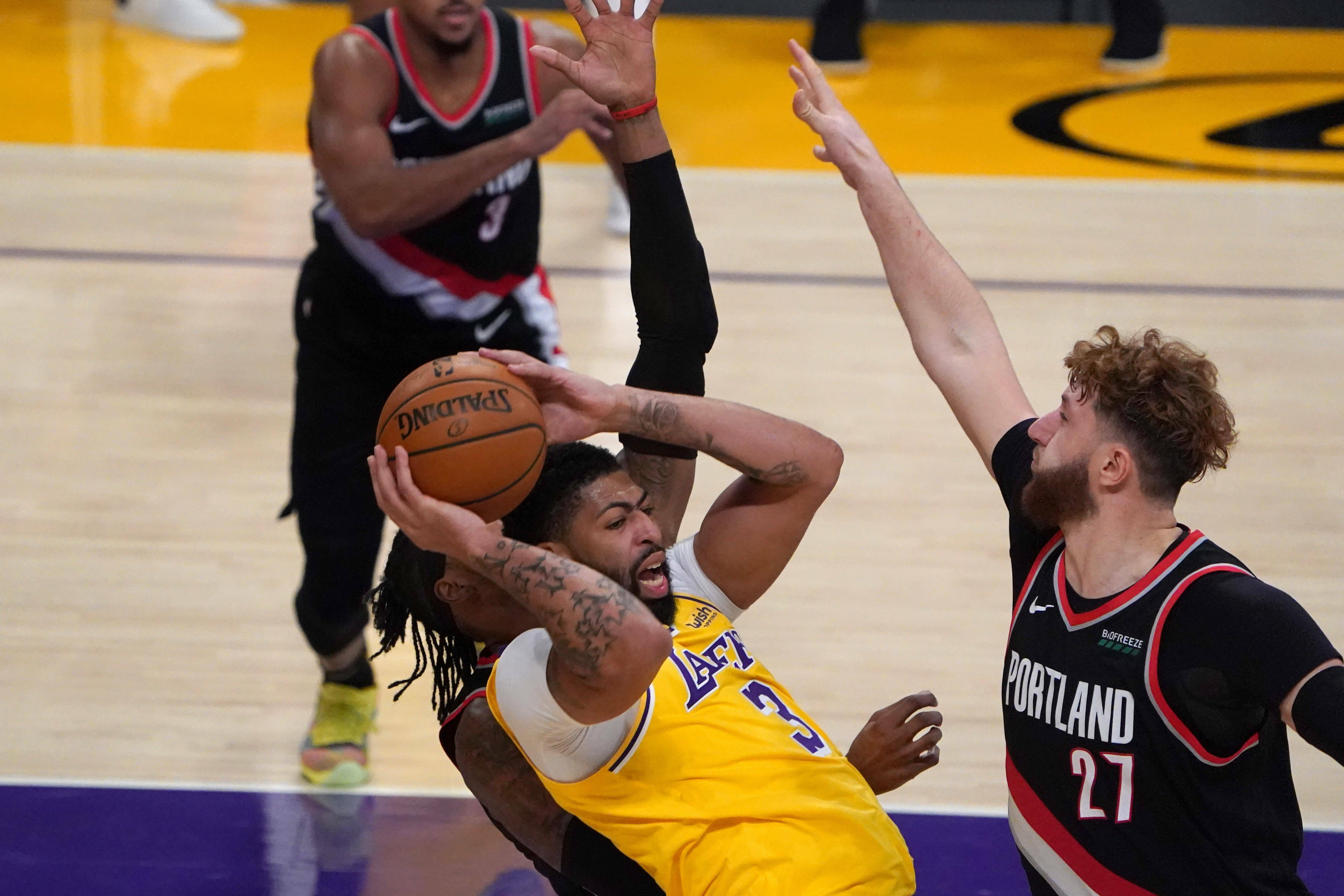 Penyerang Los Angeles Lakers Anthony Davis (3) berebut bola dengan penyerang Portland Trail Blazers Robert Covington (23) dan center Jusuf Nurkic (27)