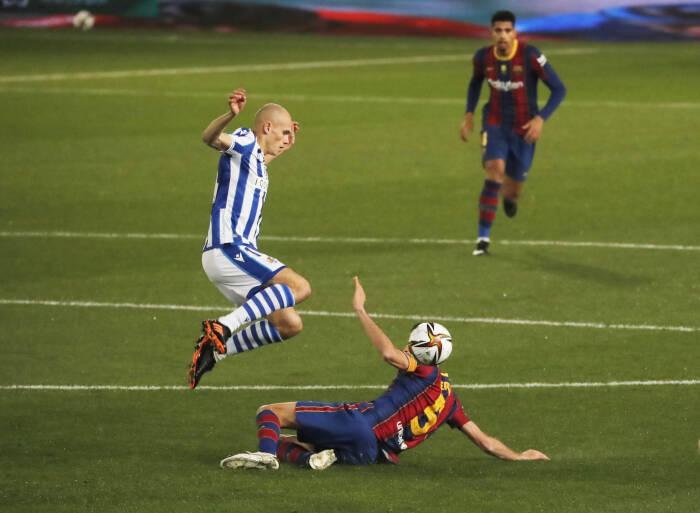 Jon Guridi dari Real Sociedad beraksi dengan Sergio Busquets dari Barcelona