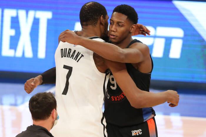 Penyerang Brooklyn Nets Kevin Durant (7) memeluk shooting guard New York Knicks RJ Barrett (9)