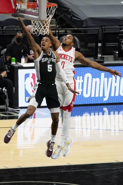 Guard San Antonio Spurs Dejounte Murray (5) menembak melewati guard Houston Rockets Sterling Brown (0)