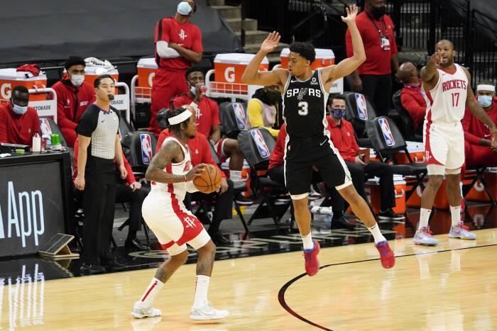 Penyerang San Antonio Spurs Keldon Johnson (3) menjaga guard Houston Rockets Ben McLemore (16)