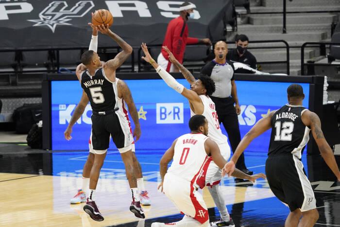 Guard San Antonio Spurs Dejounte Murray (5) menembak melewati center Houston Rockets Christian Wood (35)