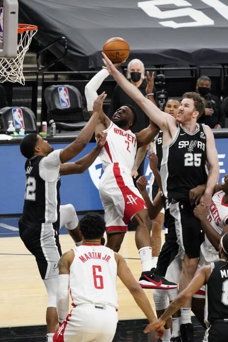 Guard Houston Rockets David Nwaba (2) menembak melewati forward San Antonio Spurs Rudy Gay (22) dan center Jakob Poeltl (25)