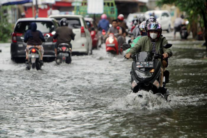 Pengendara menerobos banjir di Makassar