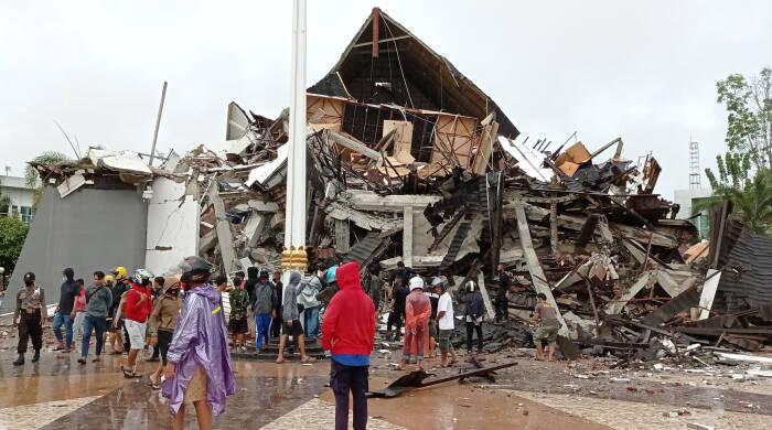 Warga mengamati Gedung Kantor Gubernur Sulawesi Barat yang rusak akibat gempa bumi, di Mamuju, Sulawesi Barat, Jumat (15/1/2021). (Antara Foto)