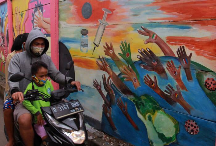Pengendara melintas disamping mural yang bertemakan kampanye melawan COVID-19