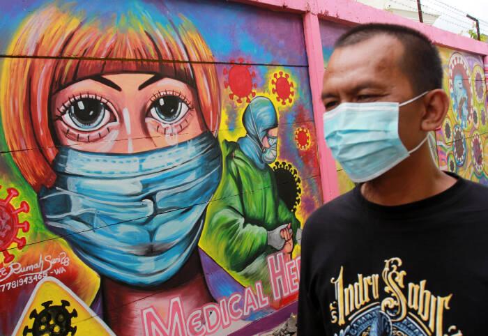 Warga melintas disamping mural yang bertemakan kampanye melawan COVID-19 (ANTARA FOTO/Muhammad Iqbal)