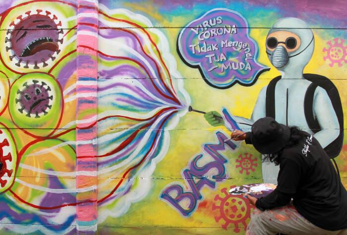 Seorang seniman mural membuat mural dengan tema kampanye melawan COVID-19