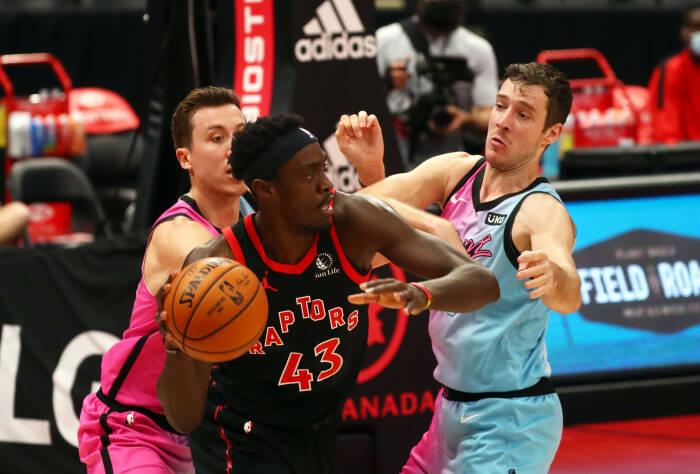 Penyerang Toronto Raptors Pascal Siakam (43) melaju ke keranjang saat guard Miami Heat Duncan Robinson (55) dan guard Goran Dragic (7) bertahan