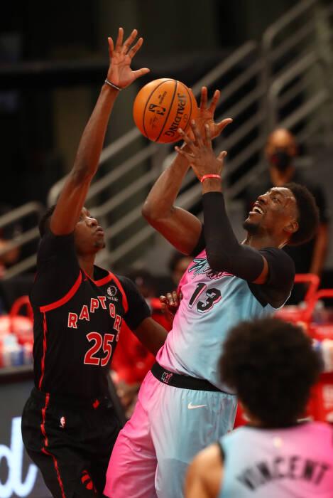 Penyerang Toronto Raptors Chris Boucher (25) menjaga center Miami Heat Bam Adebayo (13)
