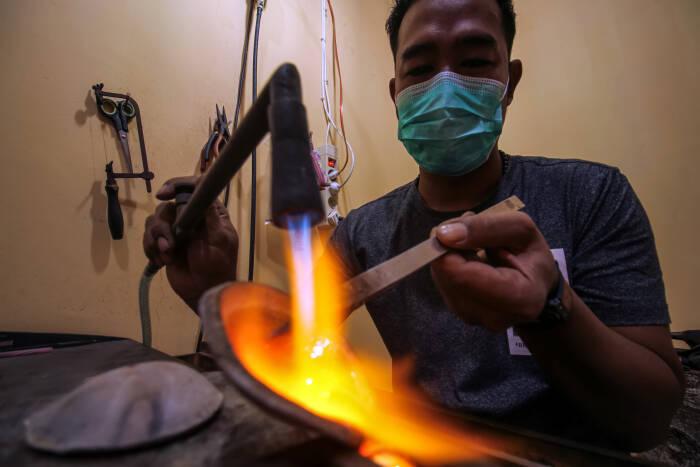 Perajin membakar perak saat pembuatan gagang cincin
