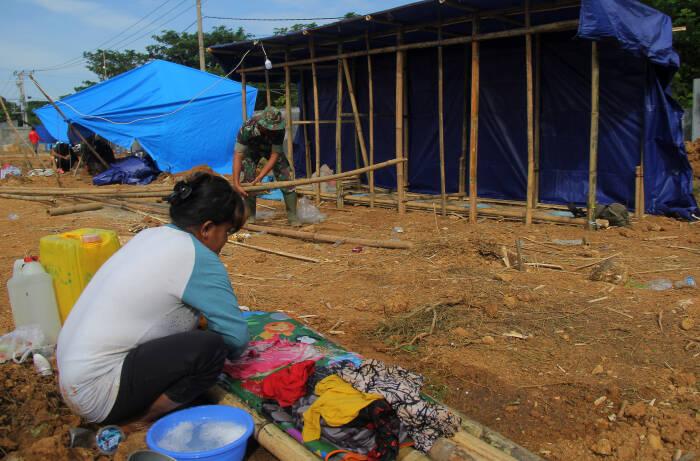 Anggota TNI membangun sarana Mandi Cuci Kakus (MCK) darurat di tenda pengungsian