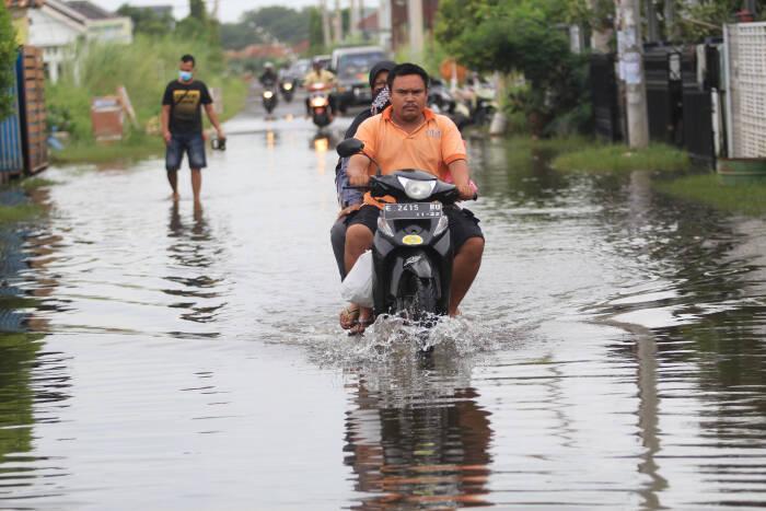 Warga menerobos genangan banjir di perumahan desa Sindang