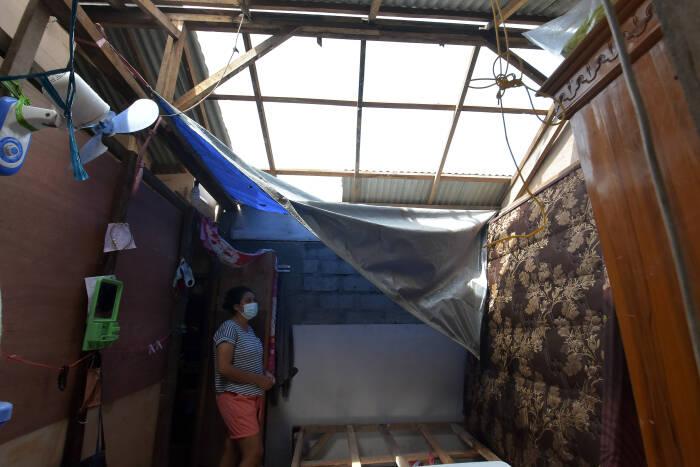 Warga melihat kondisi atap rumah kos yang rusak akibat diterpa angin puting beliung di Desa Pecatu