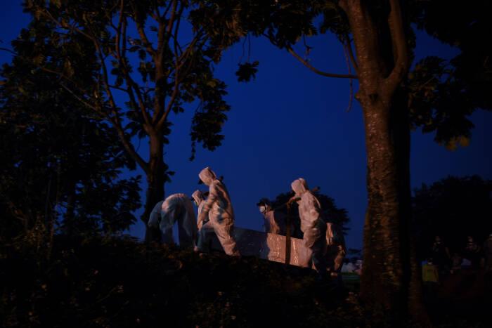 Petugas yang mengenakan APD bersiap membawa peti berisi jenazah dengan protokol COVID-19 di TPU Srengseng Sawah