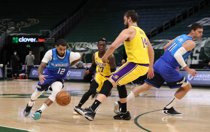 Penjaga Milwaukee Bucks D.J. Augustin (12) berusaha melewati  center Marc Gasol (14)