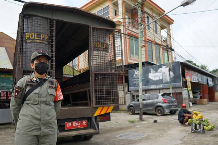 Seorang anggota Satpol PP memantau situasi jalan raya pada Operasi Yustisi