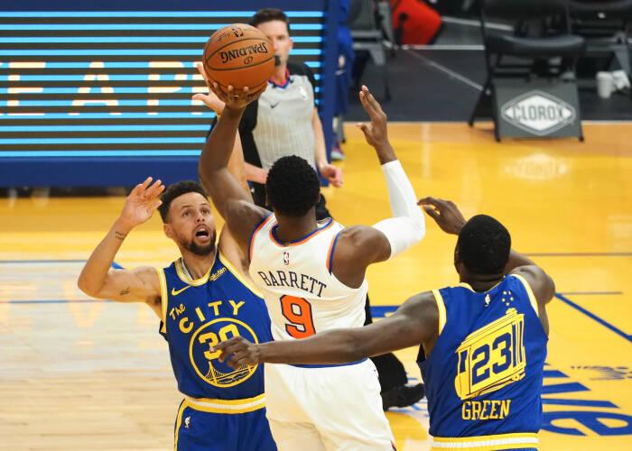Guard Golden State Warriors Stephen Curry (30) menjaga guard-forward New York Knicks RJ Barrett (9) dengan penyerang Golden State Warriors Draymond Green (23)
